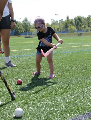 A toddler hits a ball with a field hockey stick