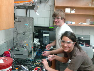 two students grin at the camera while working with a tangle of wires in front of a machine