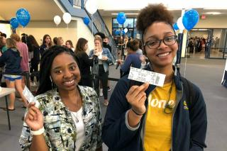 Two young women holding tickets