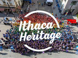 Large group of people wearing tshirts in different colors of the rainbow, with Ithaca Heritage logo