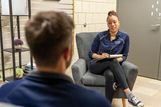 A student in a blue Ithaca College sweatshirt is seated in a chair having a conversation with another student whose back is turned to the camera.