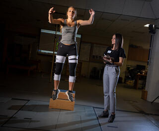 A student dressed in athletic apparel is attached to sensors and jumping up as high as they can. A student is standing next to them with a clipboard taking measurements.