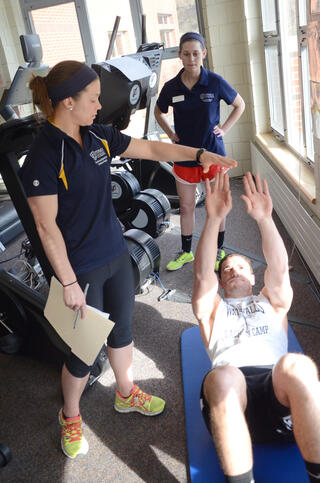 A student in a blue shirt is holding her arm straight out, while a client is lying on the floor on his back stretching his hands upward to try to touch her hand. Another student in a blue shirt and red shorts is standing in the background watching.