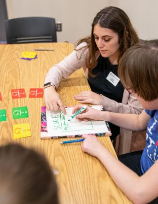 A student in a blue shirt and white sweater is seated at a table with a client heling them with a score sheet. The client is making tally marks on the score sheet related to the game they are playing.