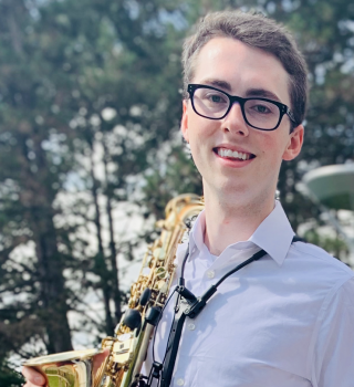 Student with alto saxophone standing outside and smiling at the camera.