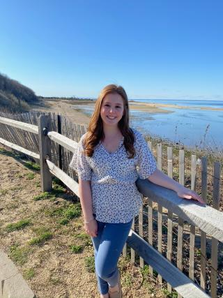 This is a photo of Danielle Frankel. Danielle is standing near a fence overlooking a lake. Danielle is wearing a flowered short-sleeve shirt and jeans.