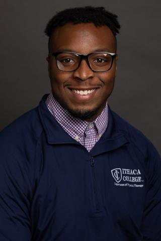 This is a photo of Olutayo Akinboboye. Olu is wearing a blue Ithaca College shirt over top of a white and blue checked shirt. Olu is wearing glasses.