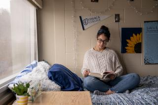 student sitting on her bed and studying in her dorm room