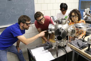 Students in chemistry and physics collaborate in a research lab.