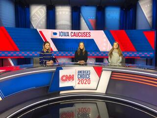 Three IC students at a news desk reporting on the 2020 primary