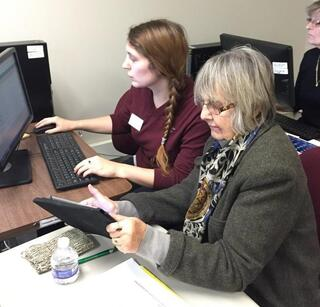 A student and a faculty member work together at a computer.