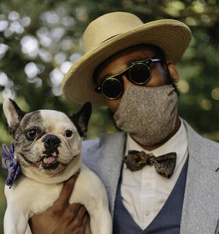 man wearing a mask, holding a dog