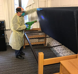 Staff member using an electrostatic sprayer