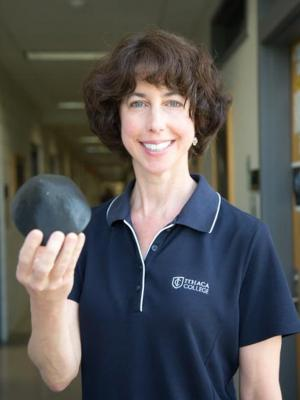Professor Beth Ellen Clark holds a model of the asteroid Bennu.