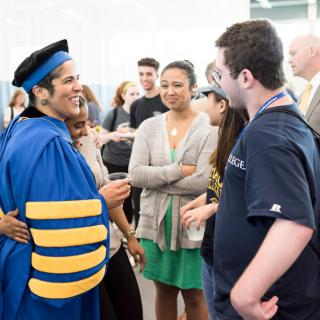 A woman in academic cap and gown being hugged by a female student while speaking with other students.