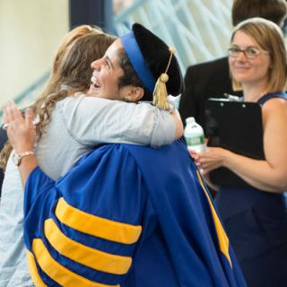 A woman in academic cap and a female student hug.