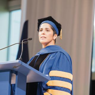 A woman in academic cap and gown stands at a podium with microphones and looks out over the crowd.