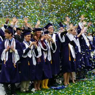 Graduates celebrate at confetti rains down.