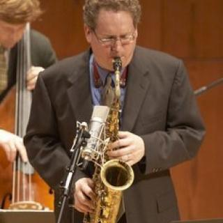Caucasian male playing a saxophone