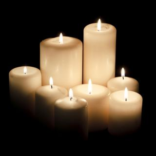 Lit candles against a dark background.