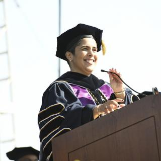 A woman in academic regalia speaking at a podium