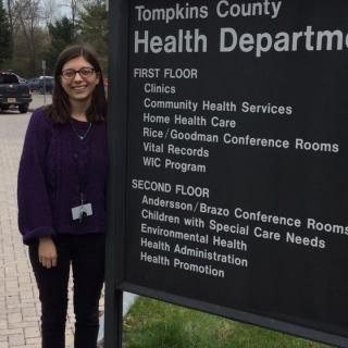 This is a picture of a student standing next to the Tompkins County Health Department sign which lists the different types of services offered such as clinics, immunizations, and vital records.