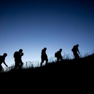 This is a picture of five students hiking up a hill with backpacks on at dusk.
