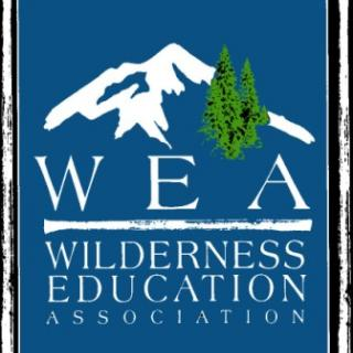 This is a logo with the picture of a mountain and some trees with the name of the organization, W, E, A or Wilderness Education Association underneath.
