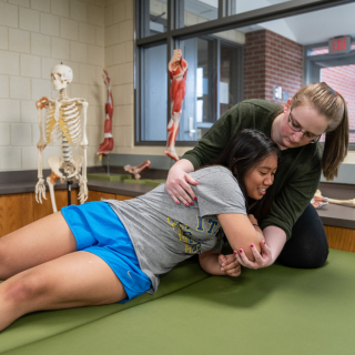 Two students are laying on a treatment plinth practicing clinical skills in a teaching lab. One student has her arms wrapped around another student stretching her shoulder and arm.