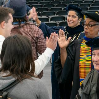 New students are given high fives by President Shirley M. Collado and Provost La Jerne Terry Cornish
