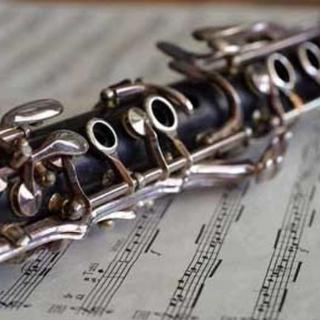 Closup of a clarinet resting on a piece of sheet music.