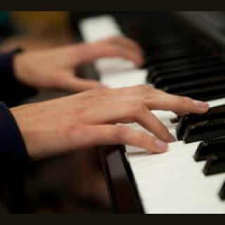 hands playing a piano keyboard