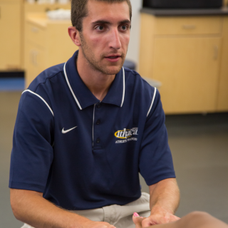 An athletic training student in a blue shirt and khaki pants is seated examining the ankle of an athlete