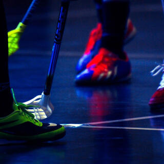 Closeup of floor hockey players' shoes and hockey sticks.